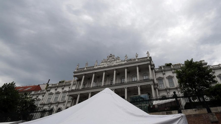 A tent a TV crew stands in front of Palais Coburg where closed-door nuclear talks with Iran take place in Vienna, Austria, Wednesday, July 8, 2015. (AP Photo/Ronald Zak)