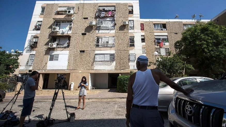 Israeli journalists report outside the apartment building of Ethiopian-Israeli Avraham Mengisto, 28, in the costal city of Ashkelon, Israel, Thursday, July 9, 2015. An Israeli security official said Thursday the Hamas militant group has been holding Mengisto in the Gaza Strip for nearly a year. The Israeli defense body responsible for Palestinian civilian affairs, said Mangisto, born in 1986 from the Israeli city of Ashkelon, independently crossed the border fence into the Gaza Strip in September last year, nearly two weeks after the end of the Israel-Gaza war. (AP Photo/Tsafrir Abayov)