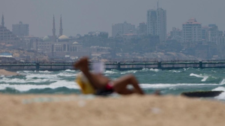 "With the Gaza strip in the background, a man reads a book as he sits on the Mediterranean sea beach near Kibbutz Zikim, on the Israel-Gaza border, near where Israeli Avraham Mangisto ""independently"" crossed the border fence into the Gaza Strip on Sept. 7 last year,  Israel, Thursday, July 9, 2015. Two Israeli citizens are being held in the Gaza Strip, at least one of them by the Hamas militant group, Israeli authorities said Thursday. Avraham Mangisto ""independently"" crossed the border fence into the Gaza Strip on Sept. 7 last year, nearly two weeks after the end of the Israel-Gaza war, the Israeli defense body responsible for Palestinian civilian affairs said, without giving further details of why he crossed into the Palestinian territory. (AP Photo/Ariel Schalit)"