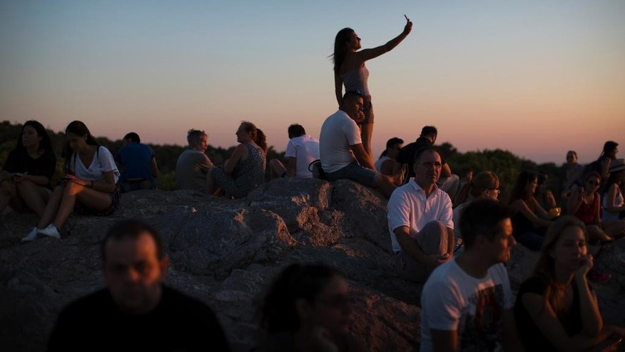 People sit in on top of a hill overlooking the city, during sunset in Athens, Wednesday, July 8, 2015. (AP Photo/Emilio Morenatti)