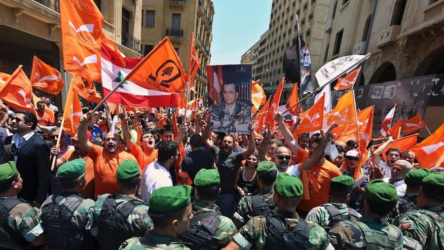 Lebanese army soldiers stand guard as supporters of Christian politician Michel Aoun chant slogans and hold flags of the Free Patriotic Movement, during a demonstration near the government headquarters in downtown Beirut, Lebanon, Thursday, July 9, 2015. Lebanese supporters of Aoun later clashed with the troops who were blocking them from reaching the prime ministry where a cabinet session is underway. (AP Photo/Bilal Hussein)