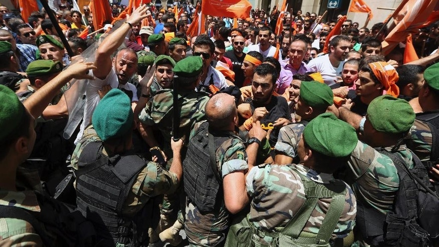 Lebanese army scuffle with supporters of Christian politician Michel Aoun during a demonstration near the government headquarters in downtown Beirut, Lebanon, Thursday, July 9, 2015. Lebanese supporters of Aoun protested and clashed with troops who blocked them from reaching the prime ministry where a cabinet session is underway. (AP Photo/Bilal Hussein)