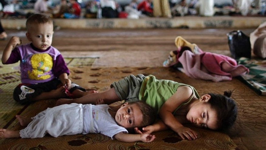 Aug. 26, 2012: Syrian children who fled their home lie on the ground while they and others take refuge at the Bab Al-Salameh border.