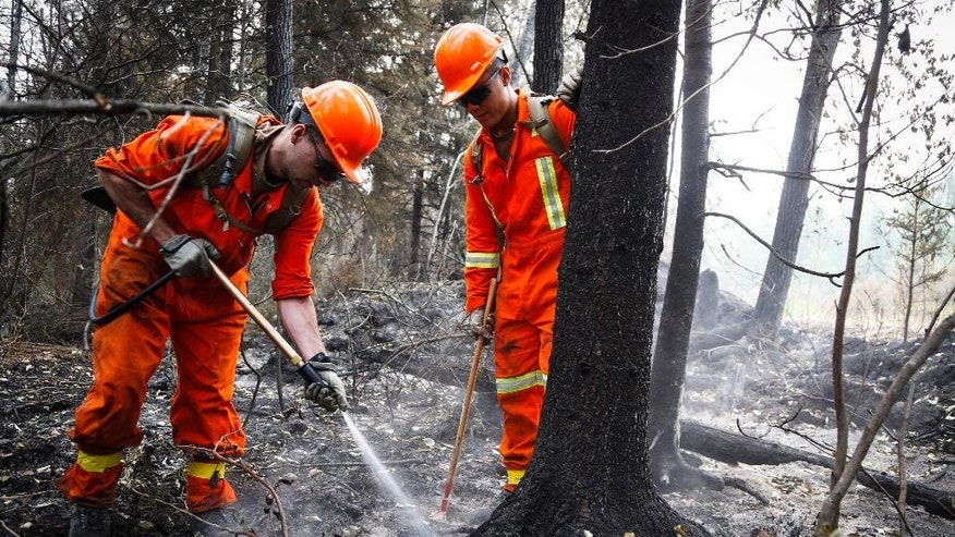 Cpl. Kevin Deng, right, and M.Cpl. Casey Zaharoff, members of the Canadian Forces, put out a hotspot from wildfires near Montreal Lake, Saskatchewan, Thursday, July 9, 2015. Large wildfires raging across Canada have contributed to a smoky haze lingering above the Western U.S., blazes fueled by the familiar hot, and dry conditions that have turned much of the region into a tinderbox. (Jeff McIntosh/The Canadian Press via AP) MANDATORY CREDIT