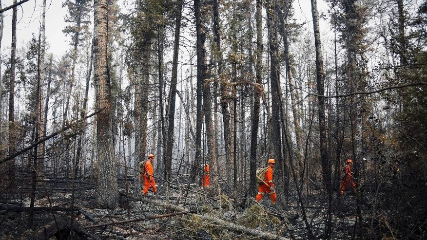 Members of the Canadian Forces look hotspots from wildfires near Montreal Lake, Saskatchewan, Thursday, July 9, 2015. Large wildfires raging across Canada have contributed to a smoky haze lingering above the Western U.S., blazes fueled by the familiar hot, and dry conditions that have turned much of the region into a tinderbox. (Jeff McIntosh/The Canadian Press via AP) MANDATORY CREDIT