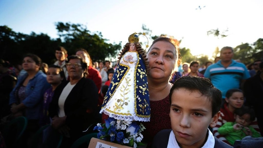 FILE - In this June 7, 2015 file photo, Mercedes Adad carries a replica of the Virgin of Caacupe as she and her son Oscar attend Mass on the feast day of Corpus Christi in Caacupe, Paraguay. When Pope Francis celebrates Mass here July 11, he'll become the second leader of the Roman Catholic Church to do so, a testament to the city's spiritual importance in Paraguay and beyond. Pope John Paul II celebrated Mass here in 1988.  (AP Photo/Jorge Saenz, File)