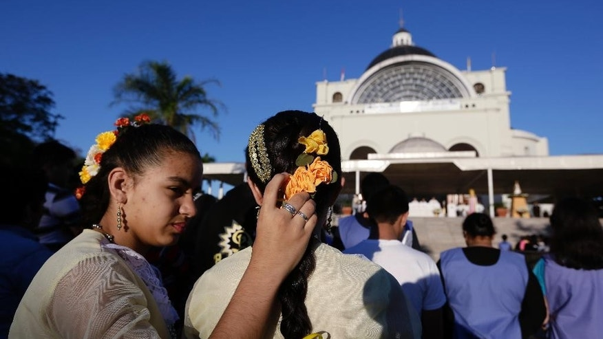 FILE - In this June 7, 2015, file photo, a girl arranges the headdress of her sister during Corpus Christi mass at shrine of the Virgin of Miracles in Caacupe, Paraguay. Lore has it that the Virgin was carved by a Guarani man named Jose, by many accounts an early convert to Christianity around the beginning of the 17th century. (AP Photo/Jorge Saenz, File)