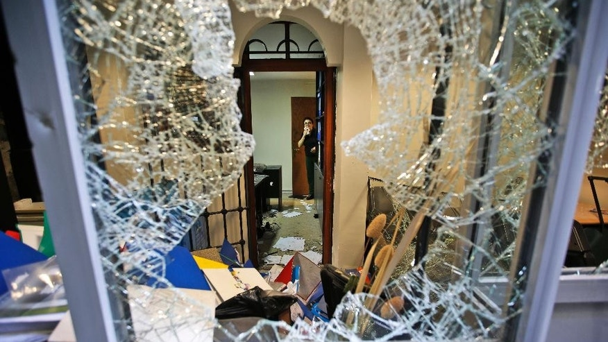 A worker inspects damage at the Thai consulate in Istanbul, Thursday, July 9, 2015. A group of protesters stormed the consulate overnight, smashing windows and breaking in to the offices, where they destroyed pictures and furniture and hurled files out into the yard, to denounce Thailand's decision to deport 109 ethnic Uighur migrants back to China. Turkey has cultural ties to the minority Muslim Uighurs and pro-Uighur groups fear the 109 face persecution by the Chinese government. (AP Photo/Emrah Gurel)