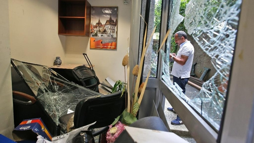 A worker inspects damage at the Thai consulate in Istanbul, Thursday, July 9, 2015. A group of protesters stormed the consulate overnight, smashing windows and breaking in to the offices, where they destroyed pictures and furniture and hurled files out into the yard, to denounce Thailand's decision to deport ethnic Uighur migrants back to China. Turkey has cultural ties to the minority Muslim Uighurs and pro-Uighur groups fear Uighurs face persecution by the Chinese government. (AP Photo/Emrah Gurel)