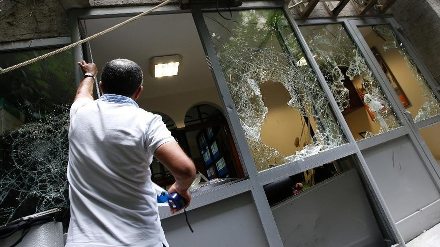 A worker measures a smashed window in order to replace it at the damaged Thai consulate in Istanbul, Thursday, July 9, 2015. A group of protesters stormed the consulate overnight, smashing windows and breaking in to the offices, where they destroyed pictures and furniture and hurled files out into the yard, to denounce Thailand's decision to deport 109 ethnic Uighur migrants back to China. Turkey has cultural ties to the minority Muslim Uighurs and pro-Uighur groups fear the 109 face persecution by the Chinese government. (AP Photo/Emrah Gurel)