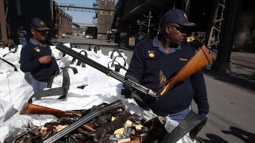 Police officers show off bags of confiscated weapons prior to being smelted at a metal processing plant in Vereeniging, South Africa, Thursday, July 9, 2015, as the world marked International Firearms Destruction Day. Over 14,000 guns were destroyed in the exercise. (AP Photo/Denis Farrell)