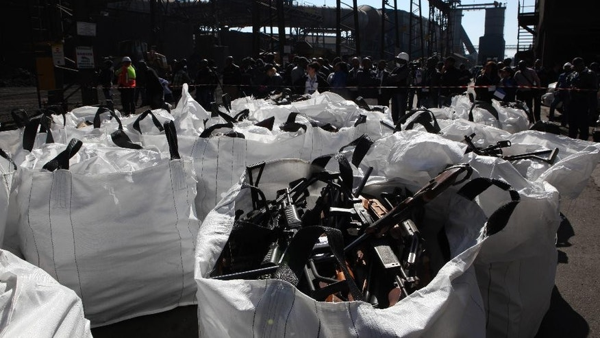Police, press and metal workers look on as bags of confiscated weapons are being prepared for smeltering at a metal processing plant in Vereeniging, South Africa, Thursday, July 9, 2015, as the world marked International Firearms Destruction Day. Over 14,000 guns were destroyed in the exercise. (AP Photo/Denis Farrell)