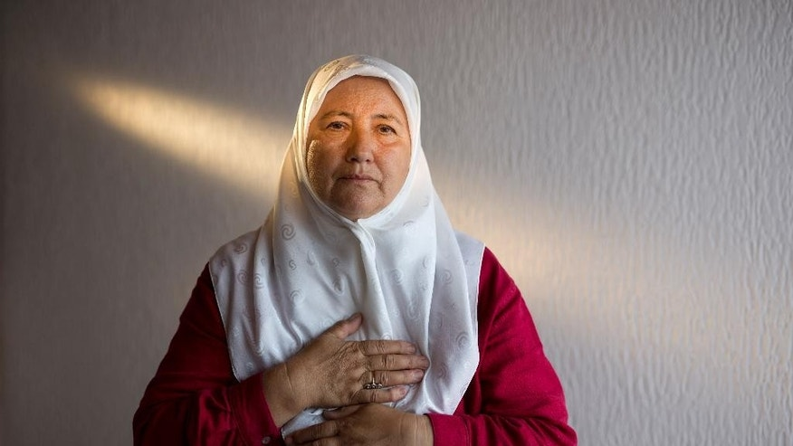 In this photo taken on Friday, July 3, 2015, Fazila Efendic, 64, poses for photo in her house in Srebrenica, Bosnia-Herzegovina.  (AP Photo/Amel Emric)