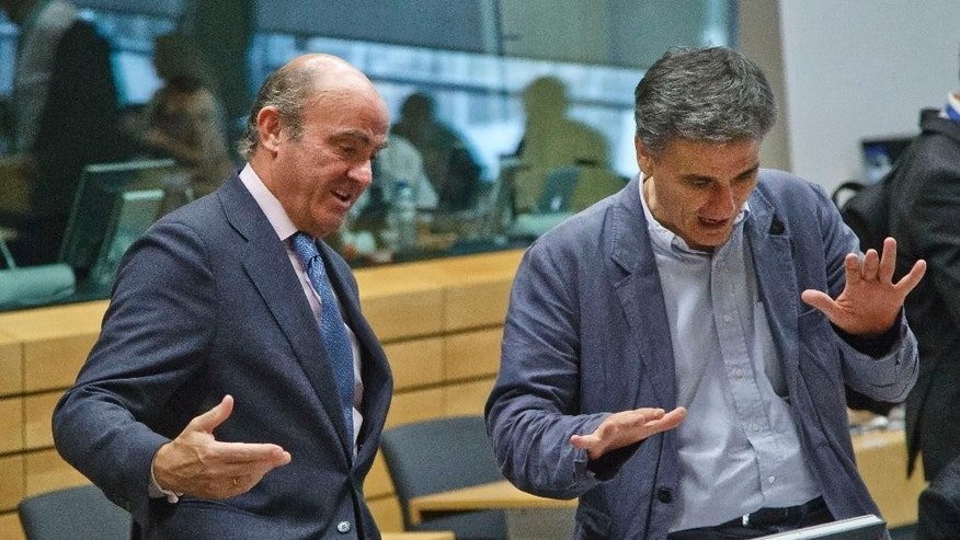 Greek Finance Minister Euclid Tsakalotos, right, speaks with Spanish Economy Minister Luis de Guindos during a round table meeting of eurozone finance ministers at the EU LEX building in Brussels on Tuesday, July 7, 2015. Greek Prime Minister Alexis Tsipras was heading Tuesday to Brussels for an emergency meeting of eurozone leaders, where he will try to use a resounding referendum victory to eke out concessions from European creditors over a bailout for the crisis-ridden country. (AP Photo/Michel Euler)