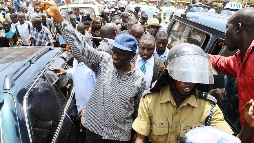 FILE - In this Wednesday, March 21, 2012 file photo, opposition leader Kizza Besigye, center, gestures the party sign before being arrested for holding a rally in Kampala, Uganda. Ugandan police said Thursday, July 9, 2015 that they have detained former Prime Minister Amama Mbabazi, who last month announced he would seek the presidency in elections next year, and also detained opposition leader Kizza Besigye, who planned to address two rallies, according to his aide. (AP Photo/Stephen Wandera, File)