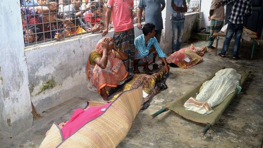 An elderly woman grieves next dead bodies at Mymensingh Medical College Hospital in the town of Mymensingh, 115 kilometers (70 miles) north of Dhaka, Bangladesh, Friday, July 10, 2015.  The victims died on a stampede when hundreds of people stormed the home of a businessman for a charity handout during the holy Muslim month of Ramadan, police said. (AP Photo/Jahangir Kabir Jewel)