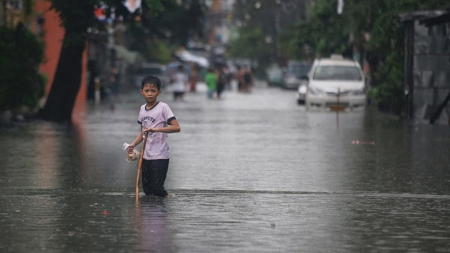 A Filipino boy carries bread as he crosses a flooded road in suburban Quezon city, north of Manila, Philippines on Thursday, July 9, 2015. Heavy rains have been drenching the capital and northern provinces as Typhoon Chan-Hom blew off the northeastern Philippines, intensifying the seasonal monsoon. (AP Photo/Aaron Favila)