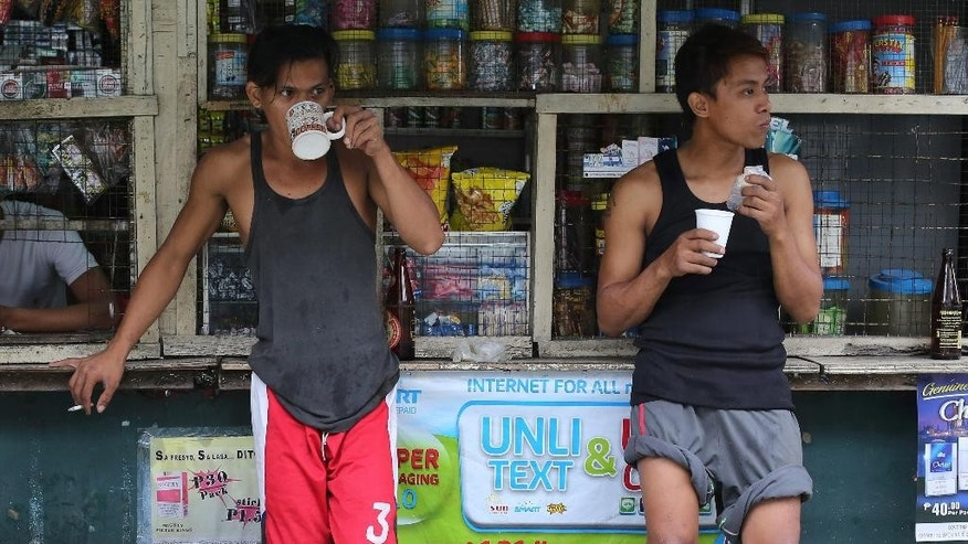 Filipino men take their coffee and snacks outside a store along a flooded road in suburban Quezon city, north of Manila, Philippines on Thursday, July 9, 2015. Heavy rains have been drenching the capital and northern provinces as Typhoon Chan-Hom blew off the northeastern Philippines, intensifying the seasonal monsoon. (AP Photo/Aaron Favila)