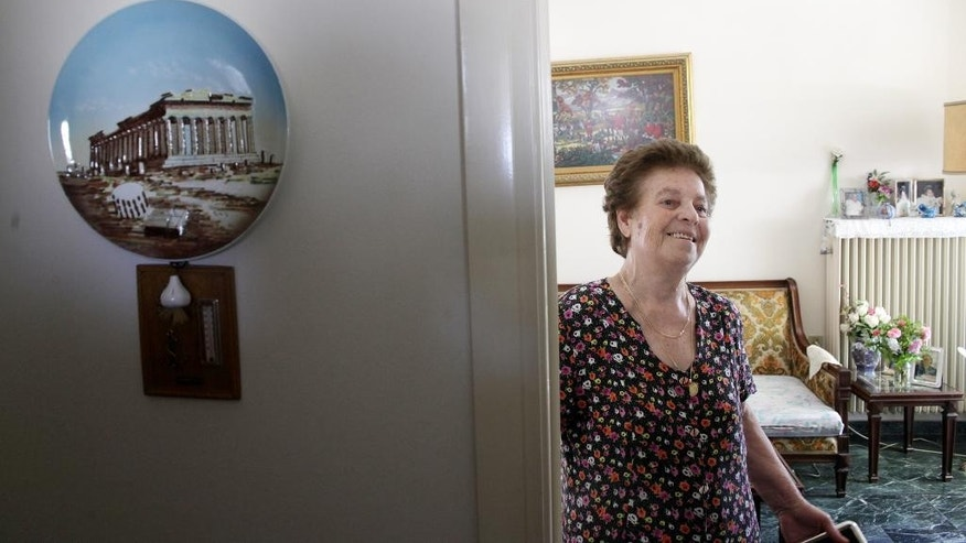 Roza Alverti, 83, smiles at her house in Athens, Friday, July 10, 2015. The Greek government is racing this weekend to approve the cuts as part of a package to be presented Sunday to European leaders in an attempt to prevent Greece from being forced to exit the eurozone group of countries. (AP Photo/Spyros Tsakiris)