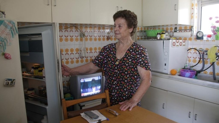 Roza Alverti, 83, opens the refrigerator at her house in Athens, Friday, July 10, 2015. The Greek government is racing this weekend to approve the cuts as part of a package to be presented Sunday to European leaders in an attempt to prevent Greece from being forced to exit the eurozone group of countries. (AP Photo/Spyros Tsakiris)
