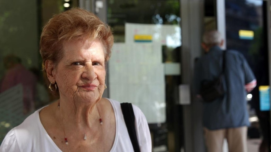 Pensioner Vassiliki Gouvousi, 80, waits outside a bank in Athens, Friday, July 10, 2015. The Greek government is racing this weekend to approve the cuts as part of a package to be presented Sunday to European leaders in an attempt to prevent Greece from being forced to exit the eurozone group of countries. (AP Photo/Spyros Tsakiris)