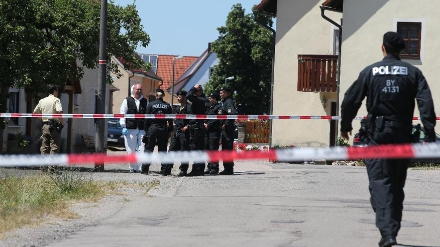 Police  inspect the scene of a shooting in  Tiefenthal near Ansbach,  Germany where a gunman has killed at least two people Friday July 10,  2015.  A man shot and killed two people in the southern German region of Bavaria on Friday, and fired at two others before being apprehended by authorities, police said.  (Daniel Karmann/dpa via AP)