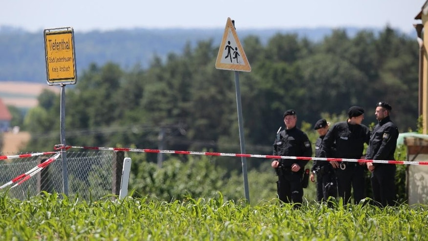 Police   guard  the scene of a shooting in  Tiefenthal near Ansbach,  Germany where a gunman has killed at least two people Friday July 10,  2015.  A man shot and killed two people in the southern German region of Bavaria on Friday, and fired at two others before being apprehended by authorities, police said.  (Daniel Karmann/dpa via AP)