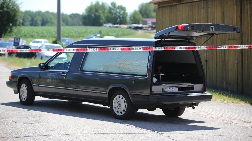 A hearse is brought to the scene of a shooting in Tiefenthal , near Ansbach,  Germany Friday July 10,  2015.  A man shot and killed two people in the southern German region of Bavaria on Friday, and fired at two others before being apprehended by authorities, police said.  (Daniel Karmann/dpa via AP)