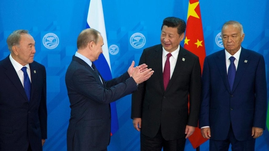 Russian President Vladimir Putin, second left, speaks to China's President Xi Jinping, second right, as Kazakhstan's President Nursultan Nazarbayev, left, and Uzbekistan's President Islam Karimov, prepare to pose for a photo during the SCO (Shanghai Cooperation Organization) summit in Ufa, Russia, Friday, July 10, 2015.   (AP Photo/Ivan Sekretarev)