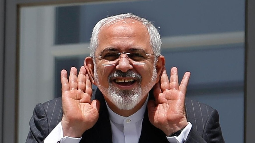 "Iranian Foreign Minister Mohammad Javad Zarif gestures to journalists from a balcony outside of the current round of Iran nuclear talks, being held in Vienna, Austria July 10, 2015.  U.S. Secretary of State John Kerry urged Iran to make the ""tough political decisions"" needed to reach an agreement but Iran's Zarif accused major powers on Friday of backtracking on previous pledges and throwing up new ""red lines"" at nuclear talks. (Carlos Barria/Pool via AP)"