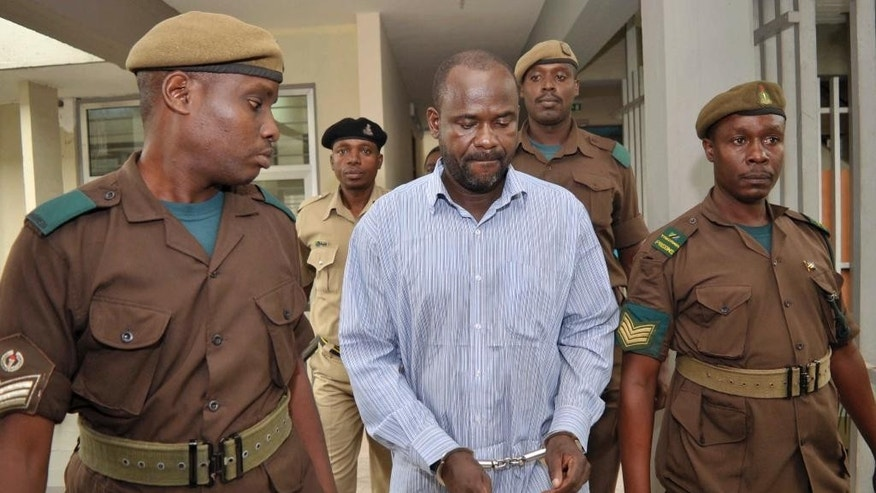 FILE - In this Friday, May 22, 2015 file photo, rebel leader of the Ugandan Allied Democratic Forces (ADF), Jamil Mukulu, center, is escorted by prison wardens as he appears at a magistrates court to challenge extradition proceedings against him, in Dar es Salaam, Tanzania.  The head of Interpol in Uganda said Friday, July 10, 2015, that Mukulu, a most-wanted Ugandan extremist who is accused of committing atrocities in Uganda and Congo, has been extradited to Uganda. (AP Photo/Khalfan Said, File)