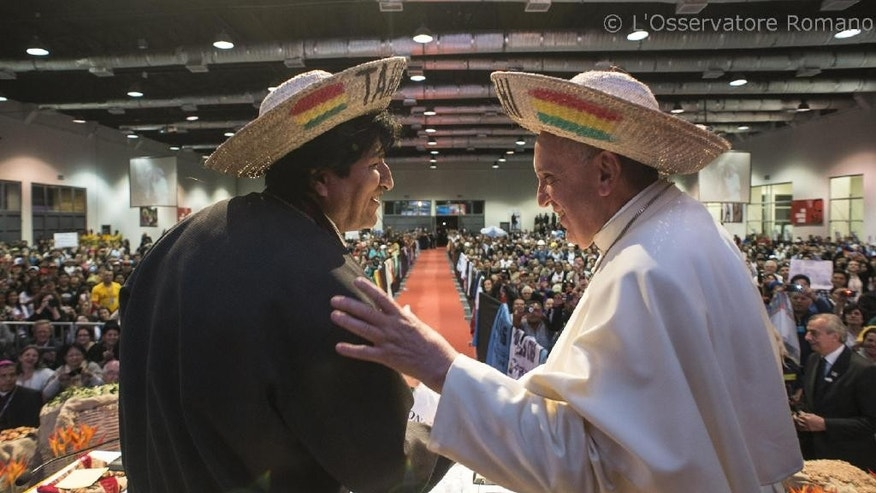 In this pool photo taken on July 9, 2015 and made available on Friday, July 10, 2015, Pope Francis and Bolivia's President Evo Morales, left, smile as they don the traditional Bolivian hats they were given at the second World Meeting of Popular Movements in Santa Cruz, Bolivia. Francis gave a late-afternoon speech to delegates at the gathering. (L'Osservatore Romano/Pool Photo via AP)