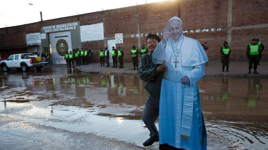 A street photographer carries a life-size cut out figure of Pope Francis, before the arrival of the pope to the Palmasola prison, behind, in Santa Cruz, Bolivia, Friday, July 10, 2015. Pope Francis wrapped up his pilgrimage to Bolivia with a visit to its notoriously violent and overcrowded Palmasola prison, where inmates have the run of the place, drugs are cheaper than on the street and money buys survival. (AP Photo/Rodrigo Abd)