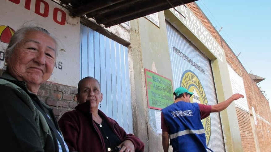 Angela Coimbra, left, the mother an inmate of the Palmasola prison, waits outside the main gate with a friend, as she attempts to deliver washing supplies to her son, in Santa Cruz, Bolivia, Thursday, July 9, 2015. Pope Francis has shown a special affection for the imprisoned since being elected pope in 2013. He will visit the Prison on Friday. (AP Photo/Jacobo Garcia)