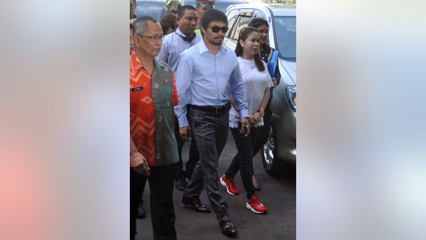 Filipino boxing icon Manny Pacquiao, center, and his wife Jinkee, right, walk upon arrival to visit their compatriot who is currently on death row for drug offenses Mary Jane Veloso at Wirogunan Prison in Yogyakarta, Indonesia, Friday, July 10, 2015. (AP Photo)