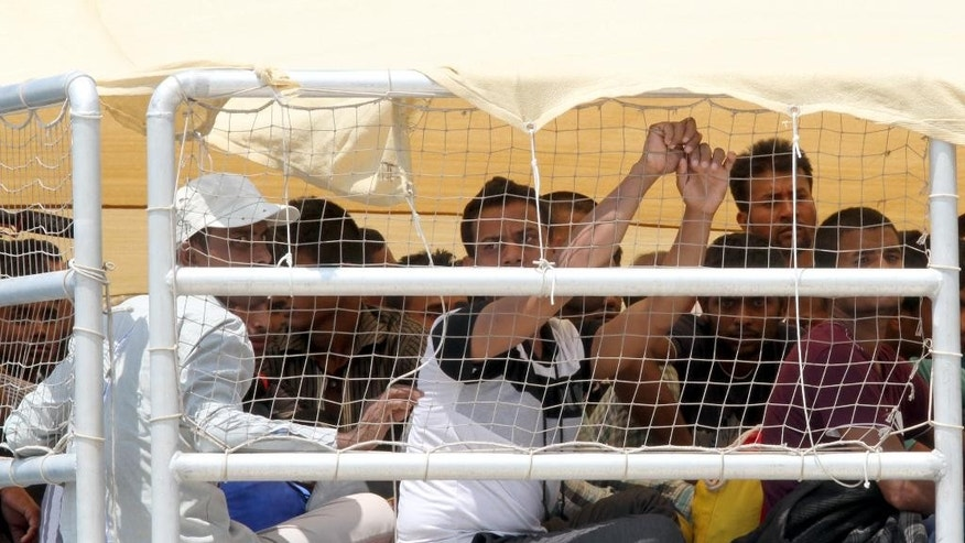 Migrants wait to disembark from the Migrant Offshore Aid Station (MOAS) ship Phoenix at the Reggio Calabria harbor, Italy, Friday, July 10, 2015. European Union ministers failed Thursday to agree on relocating 40,000 of the refugees making risky boat trips from North Africa to Italy and Greece and will try again later this month to broker a deal on how many people each country will accept. (AP Photo/Adriana Sapone)