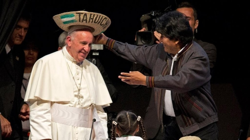 "Bolivia's President Evo Morales places a traditional Bolivian hat on Pope Francis' head during the second World Meeting of Popular Movements in Santa Cruz, Bolivia, Thursday, July 9, 2015. The Pope gave a speech to the delegates at the meeting, a collection of non-governmental organizations representing street sellers, indigenous groups, mining cooperatives and ""cartoneros,"" who sift through garbage looking for recyclable goods. (AP Photo/Eduardo Verdugo)"