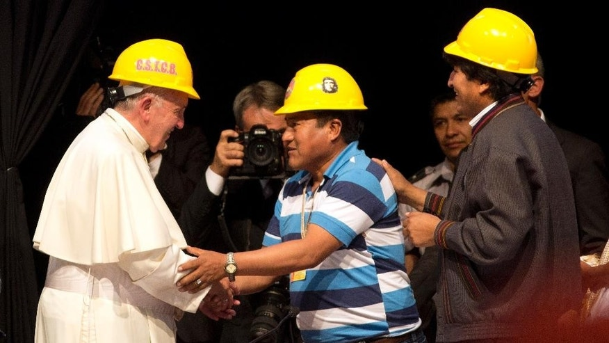 "Pope Francis shakes hands with a mining worker's leader, as Bolivia's President Evo Morales, right, stands by, during the second World Meeting of Popular Movements in Santa Cruz, Bolivia, Thursday, July 9, 2015. During his speech at the meeting, history's first Latin American pope apologized for the sins and ""offenses"" committed by the Catholic Church against indigenous peoples during the colonial-era conquest of the Americas. (AP Photo/Rodrigo Abd)"