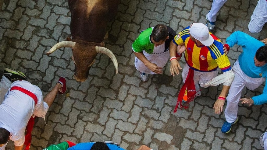 A Fuente Ymbro fighting bull runs after revelers during the running of the bulls, at the San Fermin festival, in Pamplona, Spain, Friday, July 10, 2015. Revelers from around the world arrive in Pamplona every year to take part in some of the eight days of the running of the bulls. (AP Photo/Andres Kudacki)