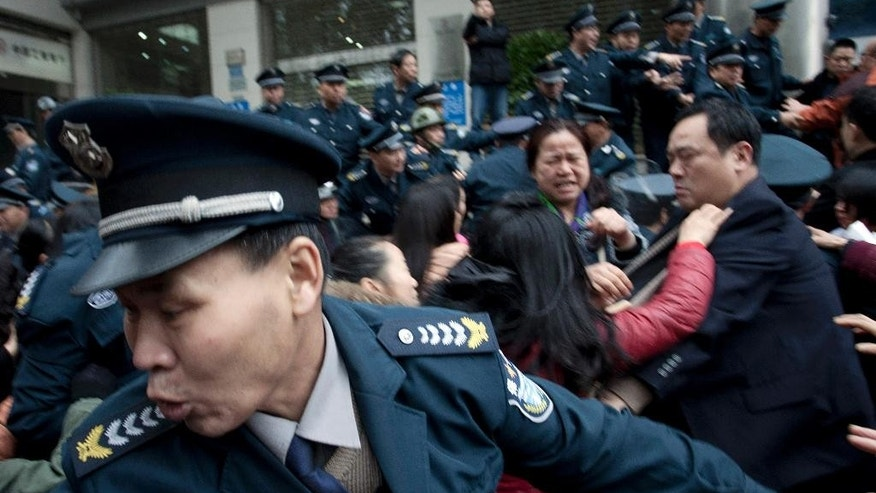 In this March 19, 2015 photo, security guards scuffle with protestors angry about failed investments with Hunan Bofeng Asset Management Ltd. outside of a branch of the Industrial and Commercial Bank of China in Changsha in southern China's Hunan province. Thousands of Chinese savers who entrusted money to an informal finance industry that operates with little government oversight are suffering painful losses as borrowers default and real estate and other ventures fail. (Chinatopix Via AP) CHINA OUT
