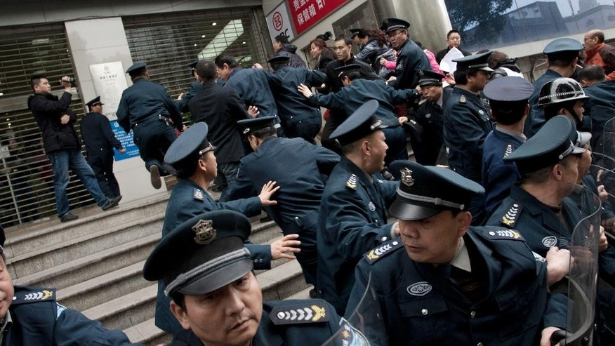 In this March 19, 2015 photo, security guards try to keep protestors angry about failed investments with Hunan Bofeng Asset Management Ltd. out of a branch of the Industrial and Commercial Bank of China in Changsha in southern China's Hunan province. Thousands of Chinese savers who entrusted money to an informal finance industry that operates with little government oversight are suffering painful losses as borrowers default and real estate and other ventures fail. (Chinatopix Via AP) CHINA OUT