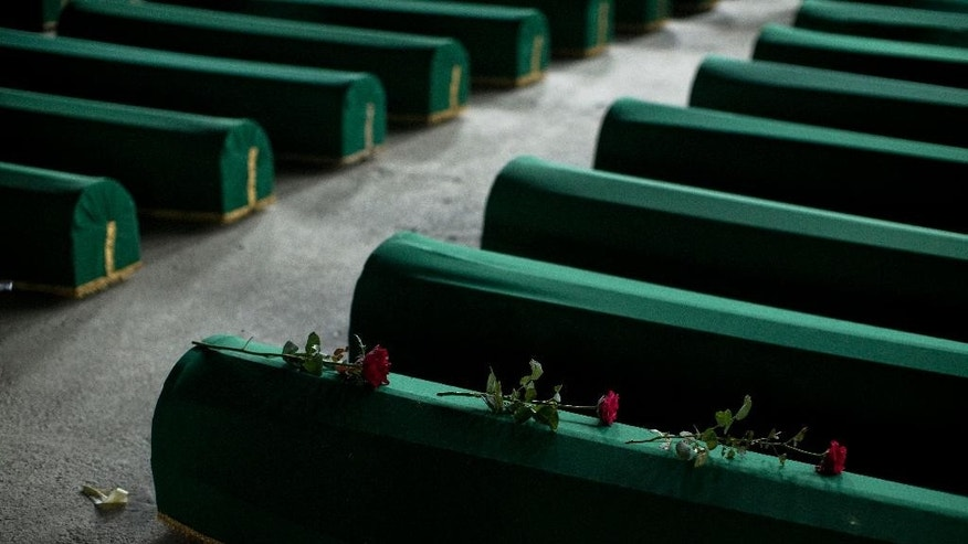 Three roses are laid on a coffin containing the remains of a person perished in the Srebrenica massacre, at the Potocari memorial complex, close to Srebrenica, 150 kilometers northeast of Sarajevo, Bosnia and Herzegovina, Thursday, July 9, 2015. The remains of 136 persons that were killed in the Srebrenica massacre will be buried at the Potocari memorial complex on Saturday, July 11, 2015, marking the 20th anniversary of what is considered to be the worst atrocity on European soil since WWII. (AP Photo/Marko Drobnjakovic)