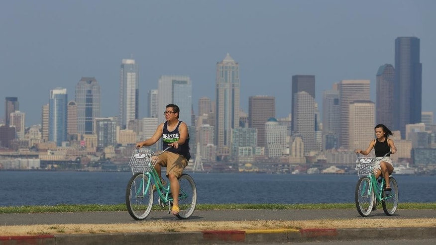 Cyclists ride on a sidewalk in West Seattle as downtown Seattle is cloaked in haze behind them, Thursday, July 9, 2015, in Seattle. Large wildfires burning in Canada are contributing to a smoky haze lingering above Seattle and other parts of the Western U.S. (AP Photo/Ted S. Warren)