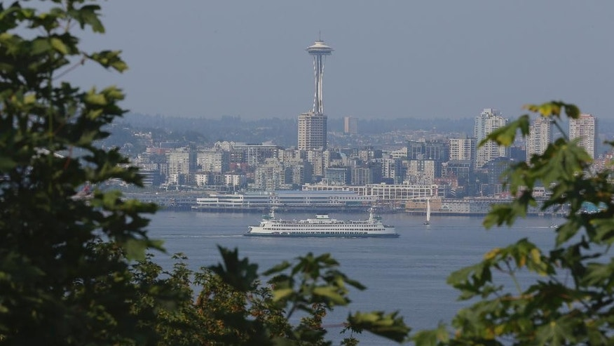 A Washington state ferry passes through Elliott Bay as seen from West Seattle as the Space Needle is cloaked in haze in the background, Thursday, July 9, 2015, in Seattle. Large wildfires burning in Canada are contributing to a smoky haze lingering above Seattle and other parts of the Western U.S. (AP Photo/Ted S. Warren)
