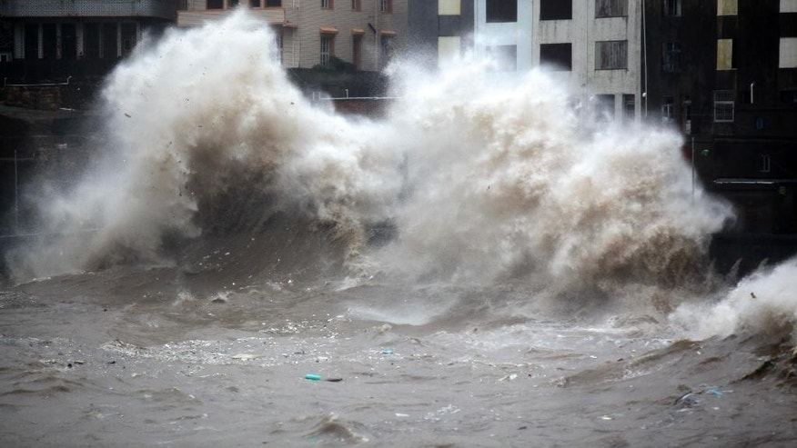 A strong wave breaks along the shore ahead of the landfall of Typhoon Chan-Hom in Wenling in eastern China's Zhejiang province Friday July 10, 2015. Chinese authorities have evacuated tens of thousands of people, canceled scores of trains and flights and shuttered seaside resorts as a super-typhoon with wind gusts up to 200 kilometers per hour (125 mph) heads toward the southeastern coast.(Chinatopix Via AP) CHINA OUT