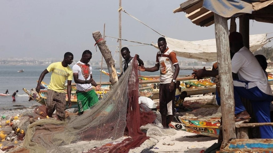 In this photo taken on Monday, June 15, 2015, fishermen repair  their fishing nets as part of preparation to go out at sea in Thiaroye, Senegal. Nearly a decade ago, Senegalese fisherman Mor Mar embarked on an illegal sea voyage to Spain, hoping a better life awaited him in Europe. High, violent waves turned the boat back, and Mar, 39, never tried to make the crossing again. Now following news reports of the more than 1,800 migrants who died this year trying to cross the Mediterranean Sea, Mar says he learned long ago to resist Europe's pull, having been turned off by stories of limited opportunity and high unemployment. (AP Photo/Babacar Dione)