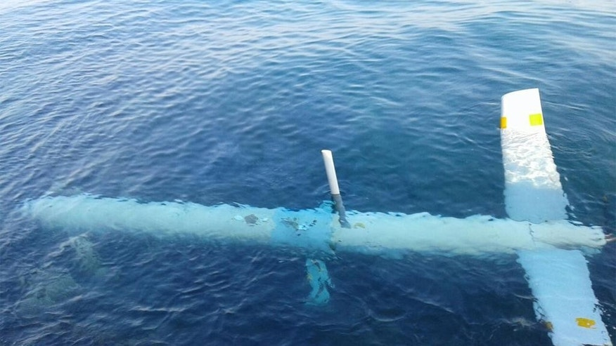 "In this photo released by the Lebanese Army official website, an Israeli drone is seen under the water in the port of Tripoli, northern Lebanon, Saturday, July 11, 2015. In a statement, the army says the unmanned reconnaissance aircraft crashed Saturday morning. It published photos that showed the aircraft largely intact in the waters and then on land after it was taken out. Arabic writing reads, ""Army public affairs."" (Lebanese Army Website via AP)"