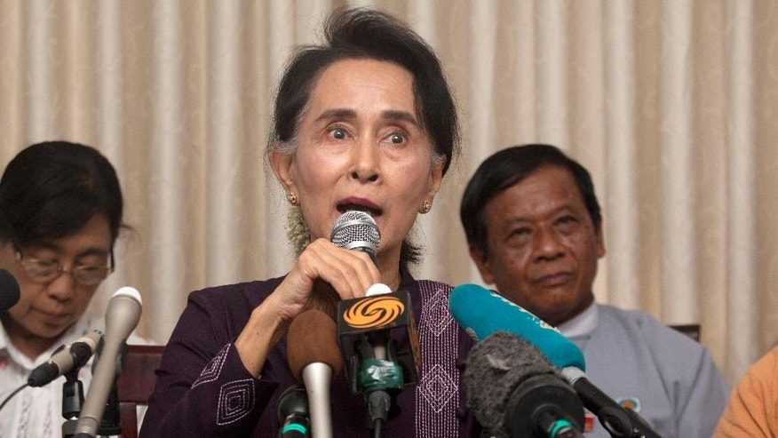 Myanmar opposition leader Aung San Suu Kyi, center, talks to journalists during a news conference at her residence, Saturday, July 11, 2015, in Naypyitaw, Myanmar. The Myanmar opposition party led by Nobel laureate Aung San Suu Kyi announced Saturday it will contest the general election on Nov. 8, an effort that is expected to strongly challenge the ruling military-backed party. (AP Photo/Khin Maung Win)
