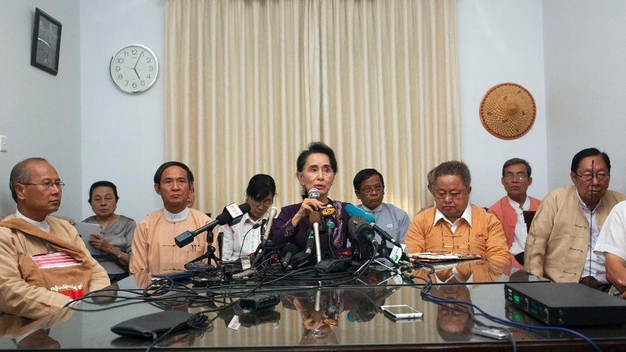 Myanmar opposition Leader Aung San Suu Kyi, center, talks to journalists during a news conference at her residence Saturday, July 11, 2015, in Naypyitaw, Myanmar. The Myanmar opposition party led by Nobel laureate Aung San Suu Kyi announced Saturday it will contest the general election on Nov. 8, an effort that is expected to strongly challenge the ruling military-backed party.(AP Photo/Khin Maung Win)