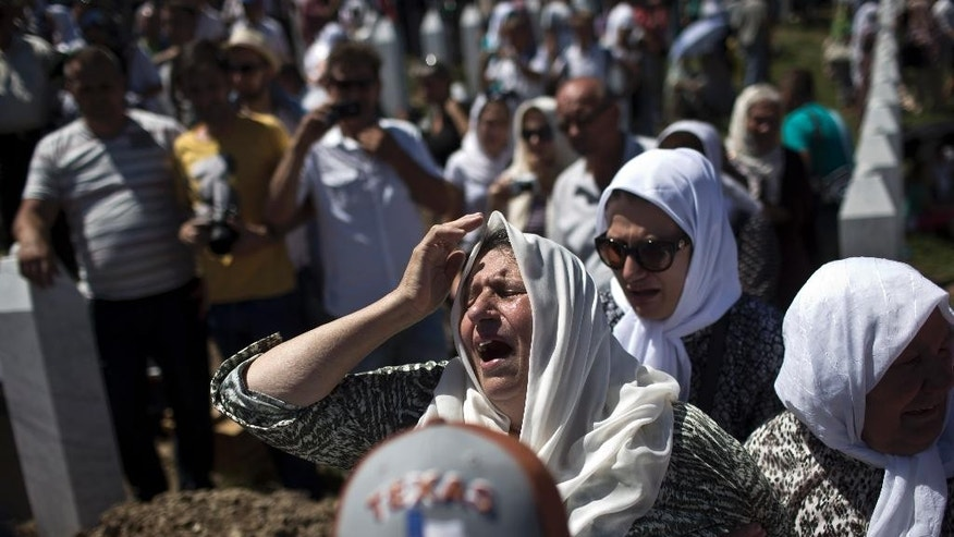 "A woman cries as the remains of her son are buried at the Potocari memorial complex near Srebrenica, 150 kilometers northeast of Sarajevo, Bosnia and Herzegovina, Saturday, July 11, 2015. Tens of thousands came to mark the 20th anniversary of Europe's worst massacre since the Holocaust, the slaughter of 8,000 Muslims from the eastern Bosnian town of Srebrenica, with foreign dignitaries urging the international community not to allow such atrocities to happen again and to call the crime ""genocide."" (AP Photo/Marko Drobnjakovic)"